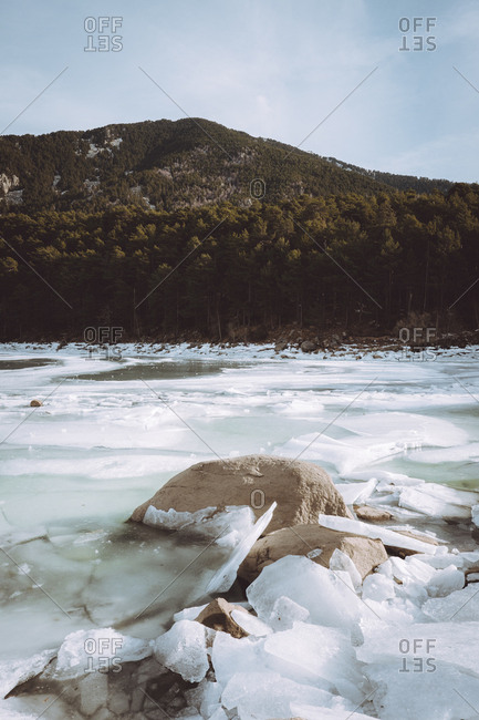 View to frozen icy river and hill covered with forest