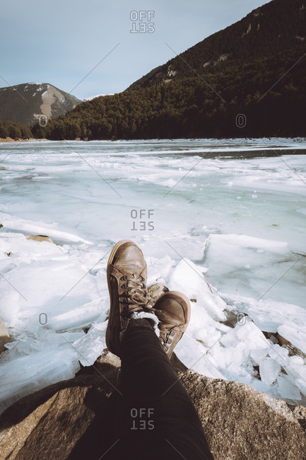 Legs of unrecognizable tourist sitting and resting and snowy icy river in mountains