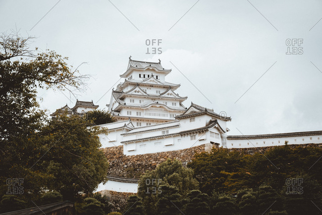 From below view of white oriental temple above green trees in cloudy day