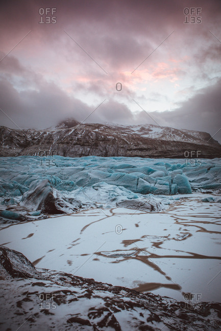 View of frost glacier surface with background of rocky cliffs in gloomy clouds