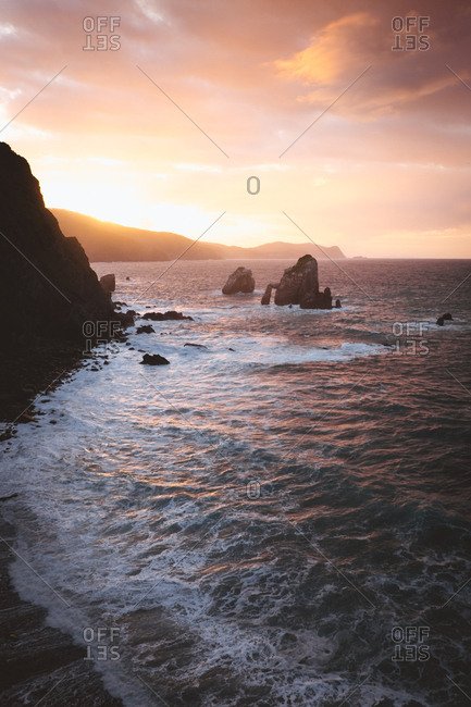 View to rocky coast and calm ocean in sunset lights