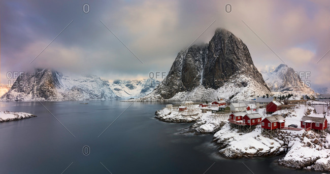 Small village with red houses at lake in snowy mountains in winter