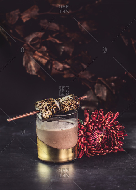 A holiday cocktail with skewered marshmallows on a tablescape