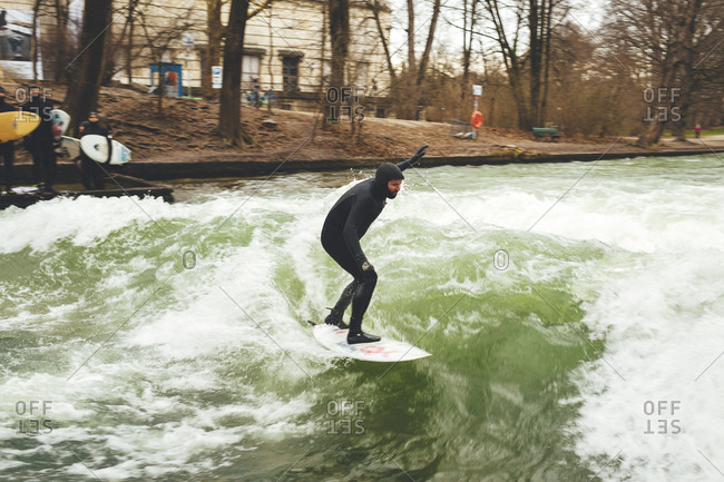 Munich, Germany - January 28, 2018: Surfer riding wave in fast flowing river