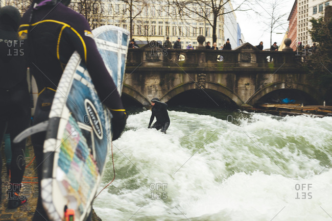 Munich, Germany - January 28, 2018: Surfer enjoying river wave in the center of town