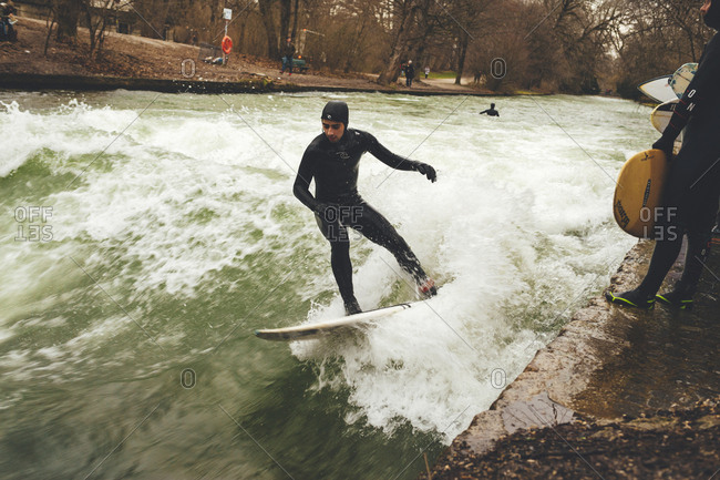 Munich, Germany - January 28, 2018: Surfer riding wave in fast flowing current of river