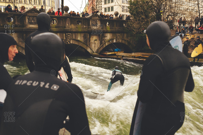 Munich, Germany - January 28, 2018: Many people watching surfer ride river wave in the center of town