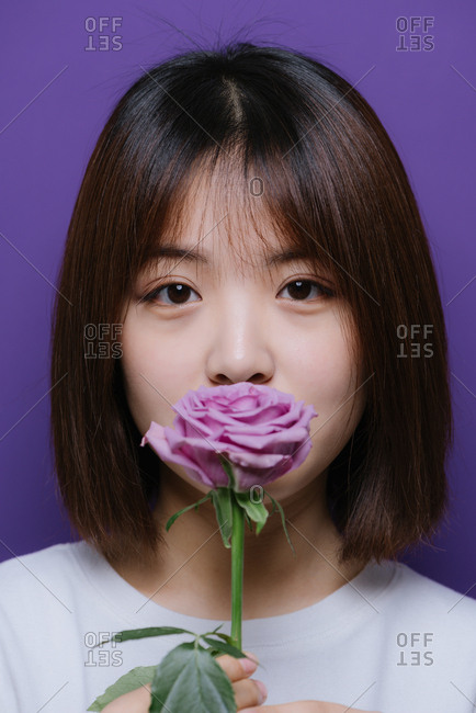 Young Chinese girl holding a single rose in front of her mouth