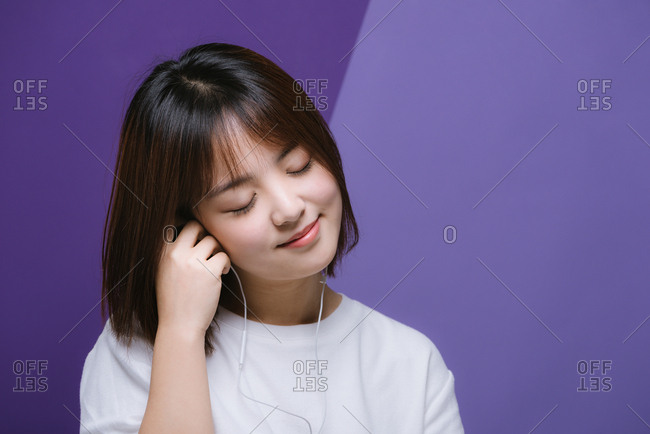 Portrait of young Chinese girl listening to headphones