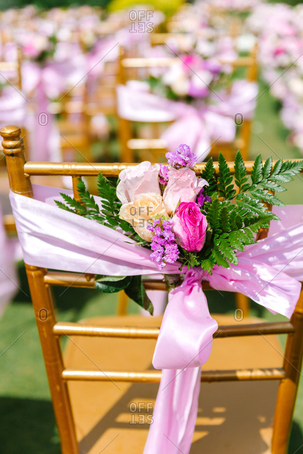 Flowers tied with ribbon on the back of a chair at a wedding ceremony