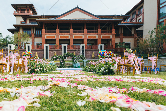 Outdoor wedding ceremony with flower petals spread on ground