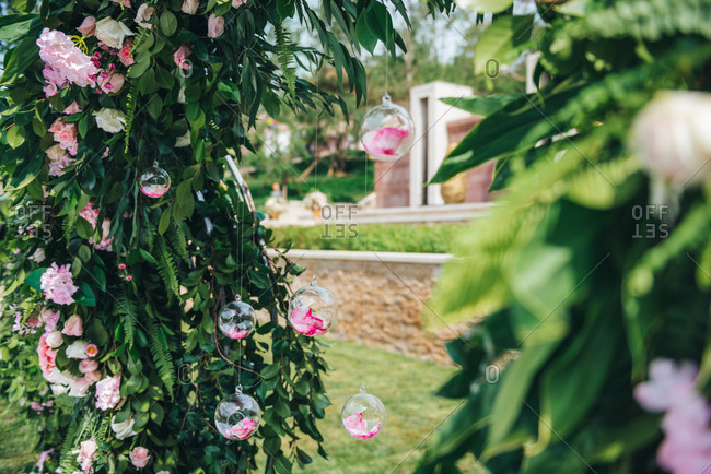 Glass bulbs filled with pink rose petals at an outdoor wedding ceremony