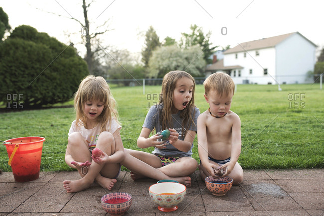Kids dyeing Easter eggs outside