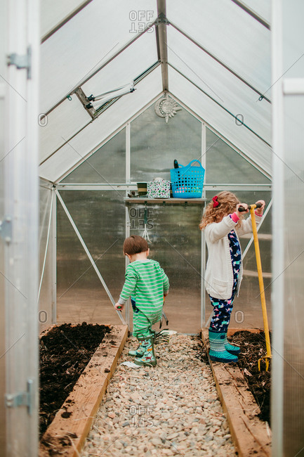 Young siblings working in greenhouse together