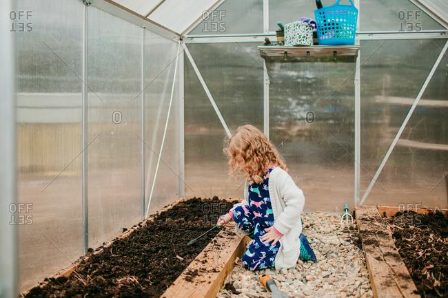 Girl digging through soil in greenhouse