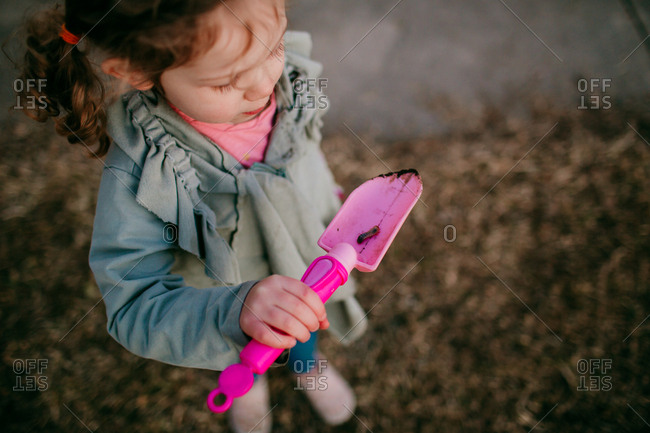 Little girl examining a worm on toy shovel