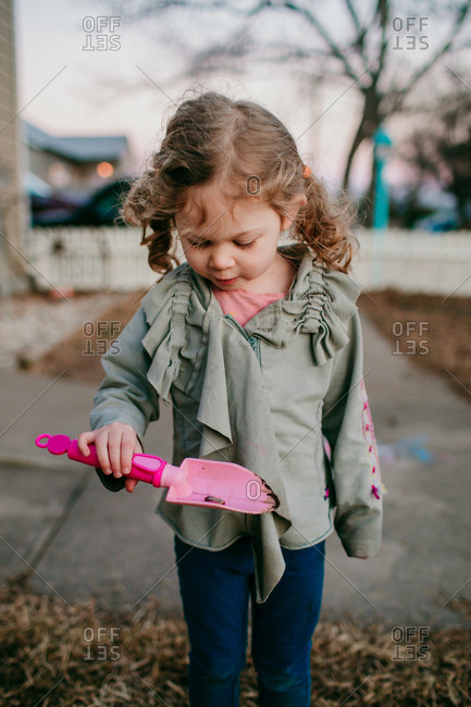Curious young girl observing bug on toy gardening tools