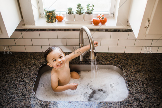 Little toddler taking a bath in the sink