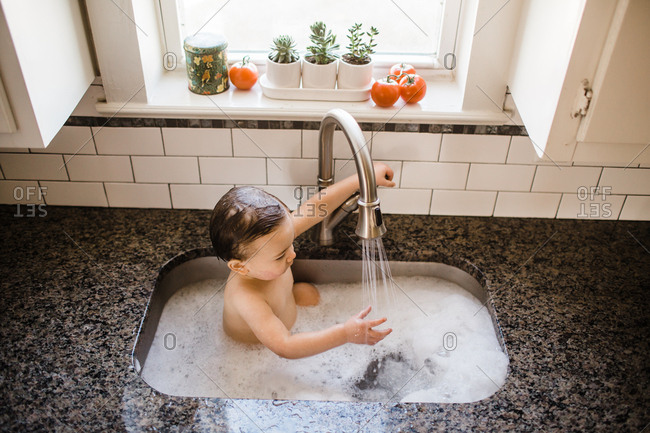 Bathing child watching faucet in kitchen sink