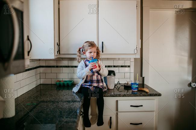 Toddler girl enjoying smoothie on countertop