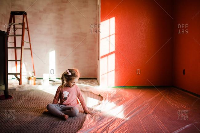 Little girl feels floor plastic in fresh painted bedroom
