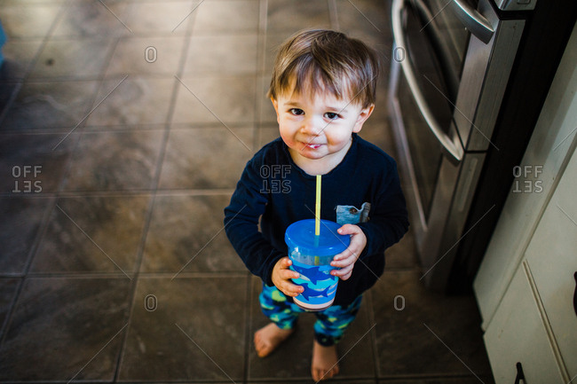 Happy toddler in kitchen with smoothie