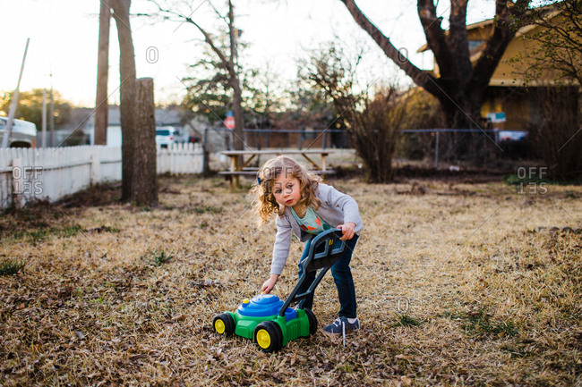 Girl playing outside with toy lawn mower