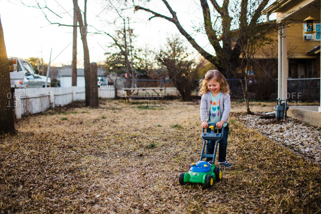Little girl pretending to mow the lawn