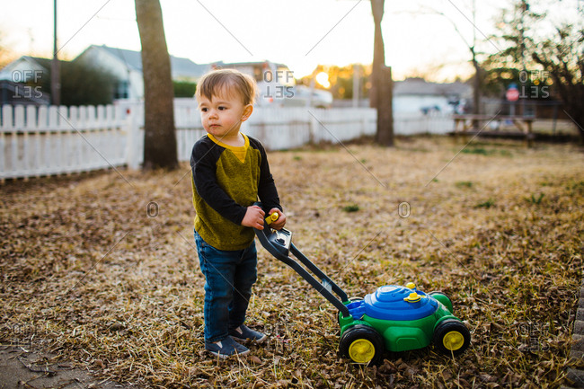 Toddler pausing with toy lawn mower in yard
