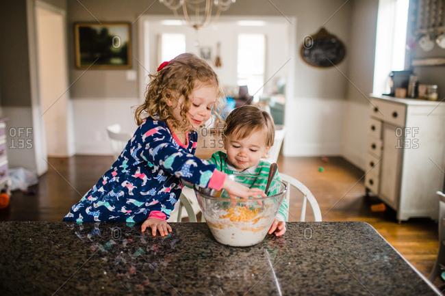 Kids reaching into mixing bowl to taste test recipe