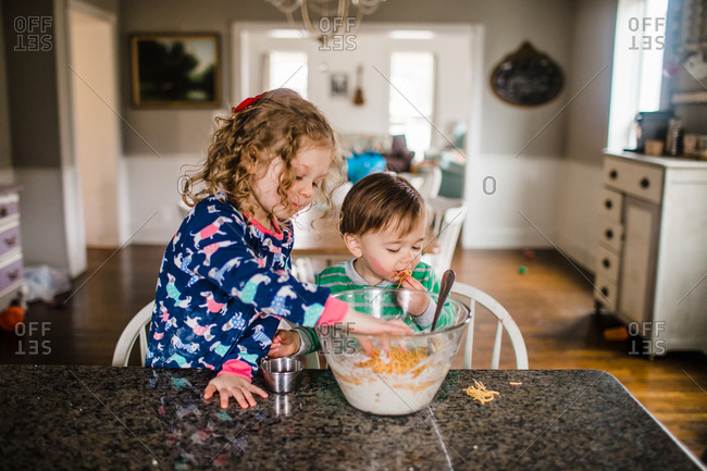 Brother and sister testing shredded cheese from mixing bowl