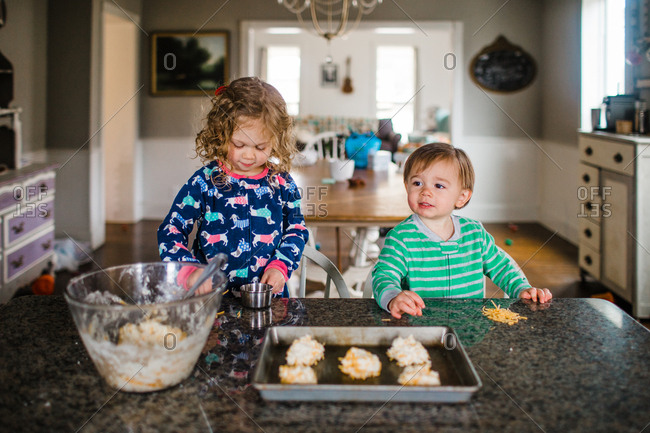 Kids placing biscuit dough onto tray for baking