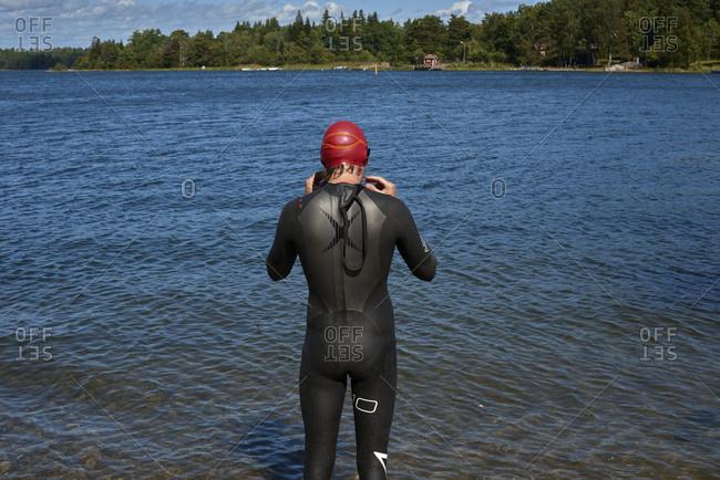 Man standing in wetsuit in river