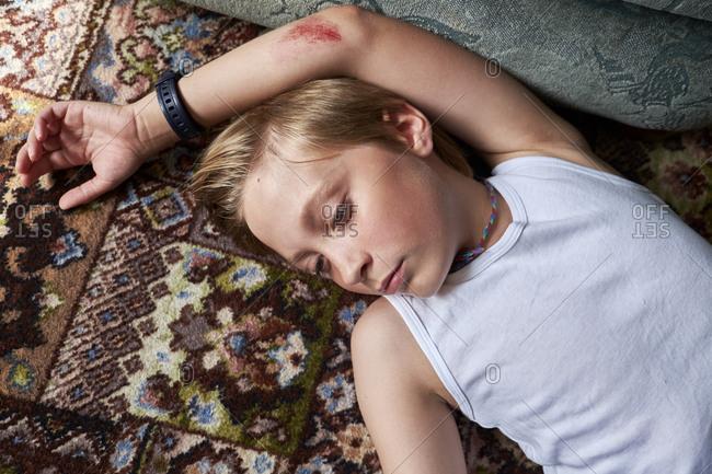 Boy lying on carpet