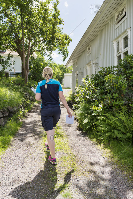 Young female mail carrier walking on footpath