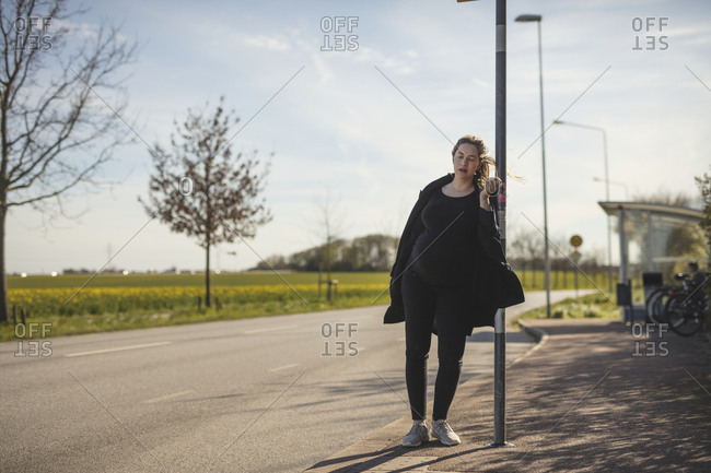 Pregnant woman standing at bus station