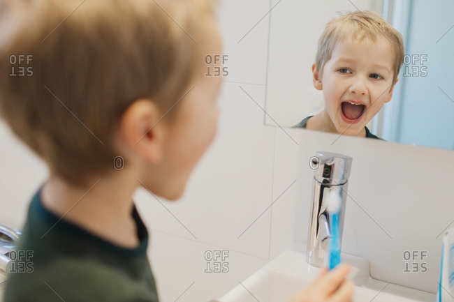 Reflection of boy brushing teeth