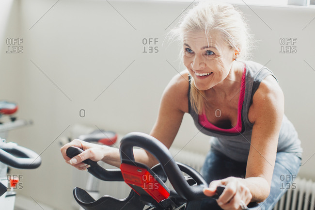 Woman exercising on stationary bicycle in gym