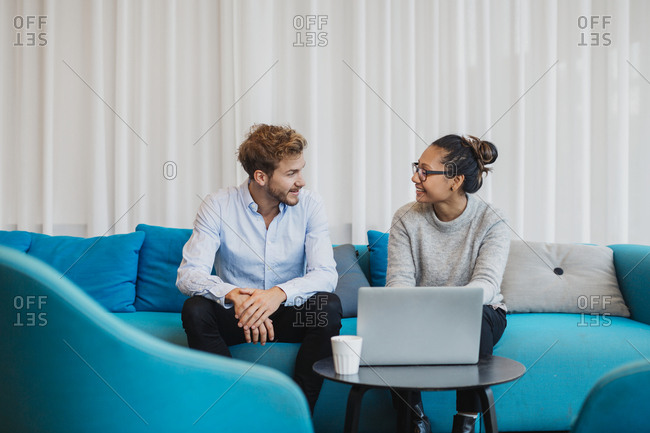 Two friends sitting in living room with laptop