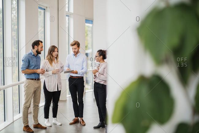 Four people talking in corridor