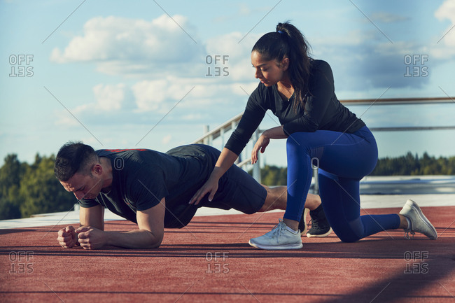 Woman kneeling next to man doing plank position