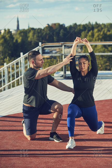 Man kneeling next to woman doing lunge exercise