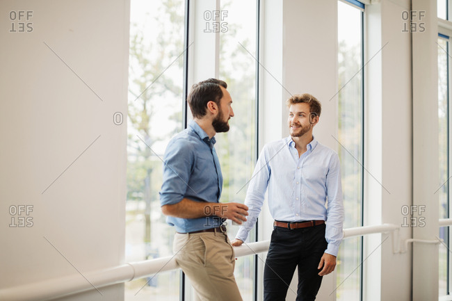 Two men talking in corridor