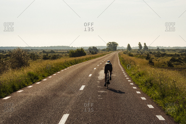 Person cycling on country road