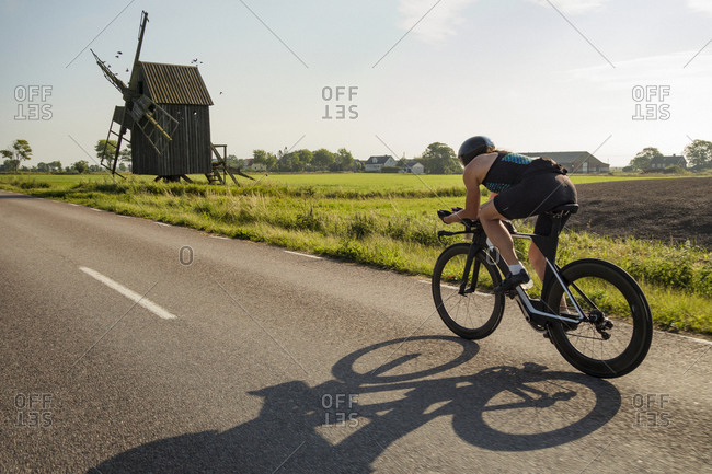 Woman cycling on country road