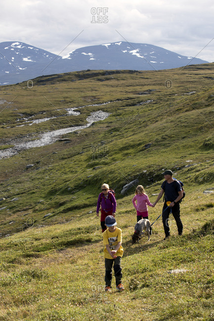 Family trekking in meadow - Offset