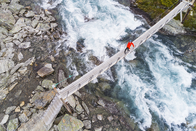 Person standing on footbridge above river