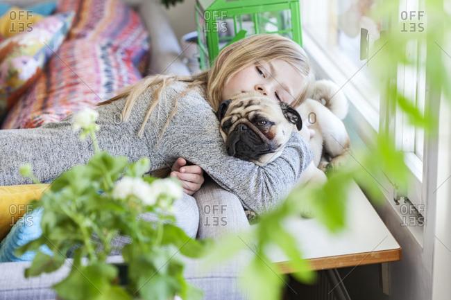 Girl hugging pug dog in living room