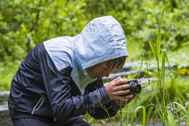 Boy photographing plants