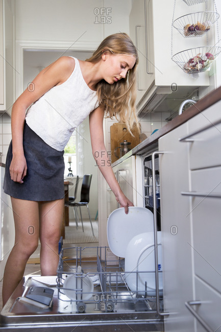 Girl putting dishes in dishwasher
